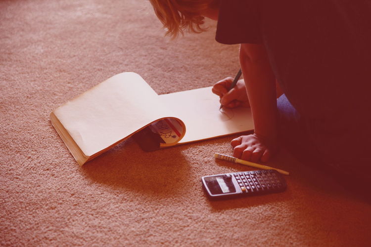Cropped image of boy drawing in book at home