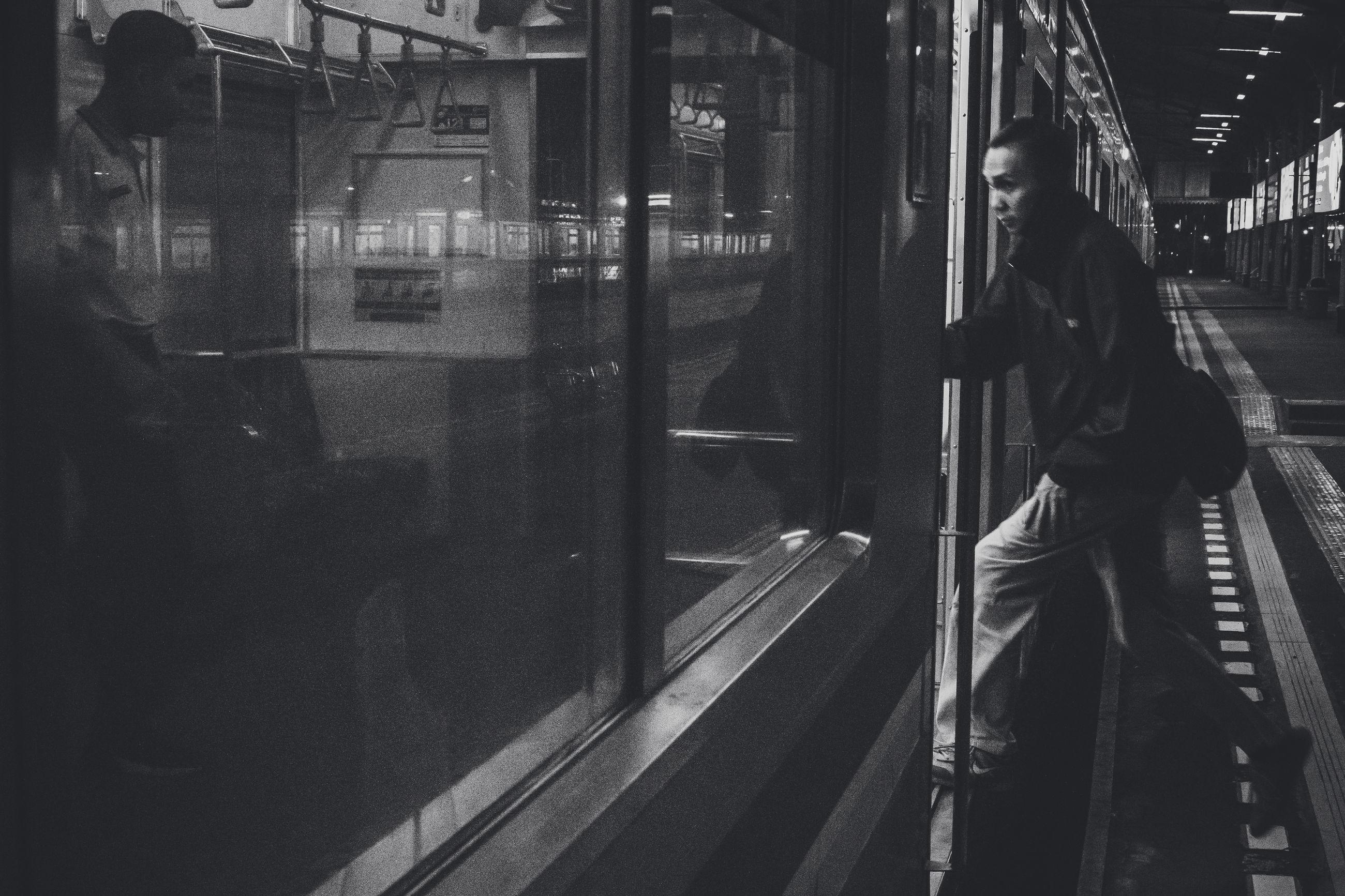 rail transportation, transportation, real people, public transportation, mode of transportation, train, train - vehicle, people, architecture, travel, railroad station platform, lifestyles, night, passenger, railroad station, reflection, city, window, motion