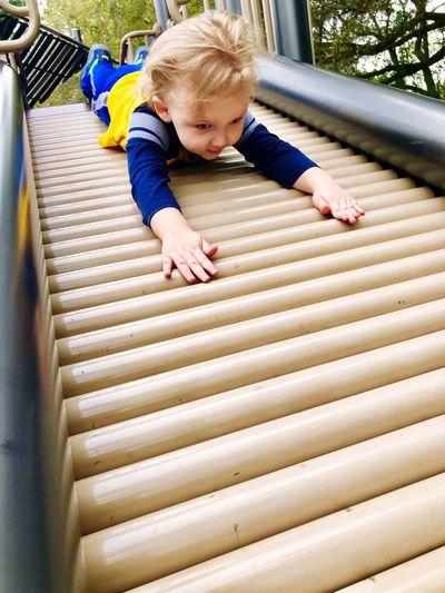 Cute boy plying on slide in playground