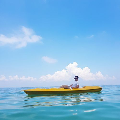Side view of man sitting on rowboat in sea against sky