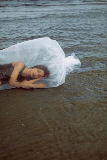Portrait of woman lying on shore