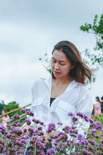 Beautiful woman standing by flowering plants against sky