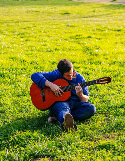 Full length of man playing guitar on field