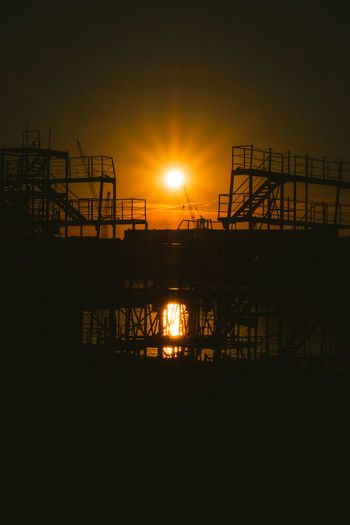 Sunset Sky Sun Industry Silhouette Built Structure Nature Orange Color Architecture Water Reflection No People Construction Industry Machinery Beauty In Nature Outdoors Construction Site Scenics - Nature Tranquility Construction Equipment