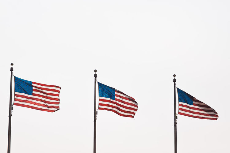 Low angle view of american flags fluttering against clear sky