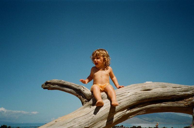 Full length of shirtless boy sitting against blue sky