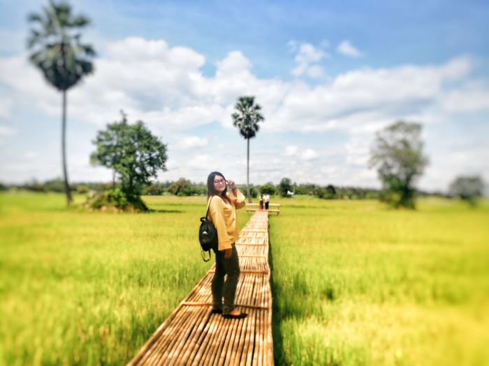 Side view of woman standing on boardwalk at rice paddy against cloudy sky