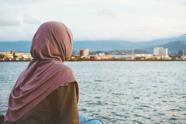 Rear view of woman looking at view of sea while sitting in city