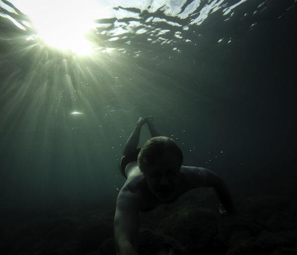 Full length of shirtless boy swimming in sea