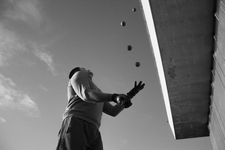 Low Angle View Of Man Playing With Balls