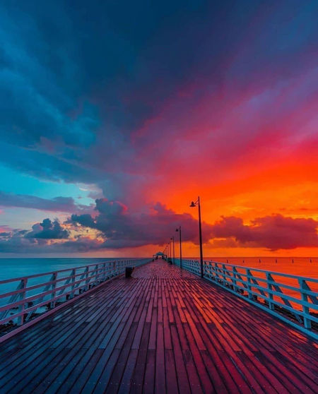 Pier over sea against dramatic sky during sunset
