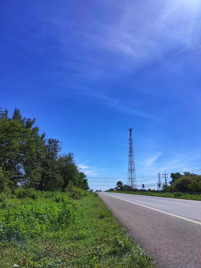 Road by telecommunication tower against blue sky
