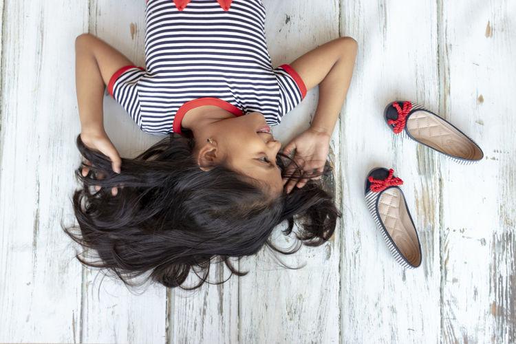 High angle view of girl looking away while lying on hardwood floor