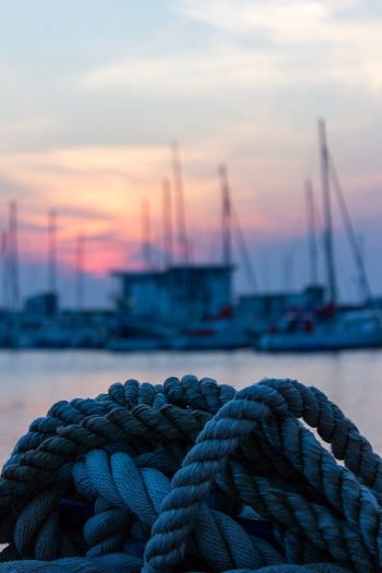 Close-up of rope tied to moored at harbor during sunset