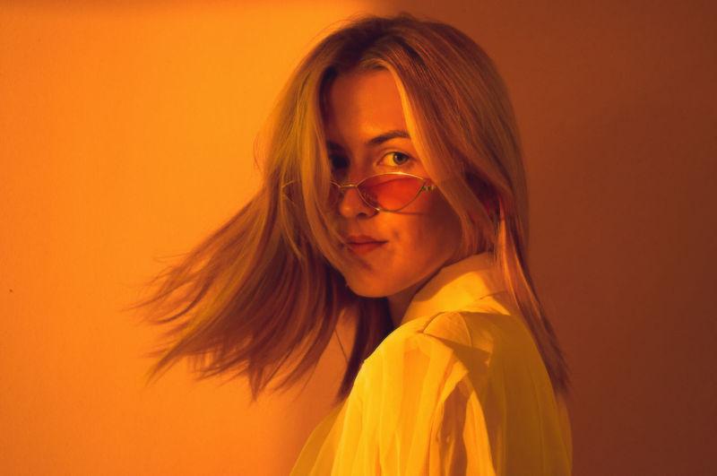 Portrait of woman against orange background