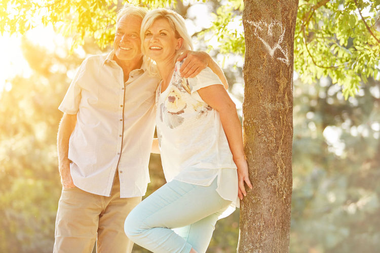 Portrait Of Smiling Senior Couple Standing By Tree