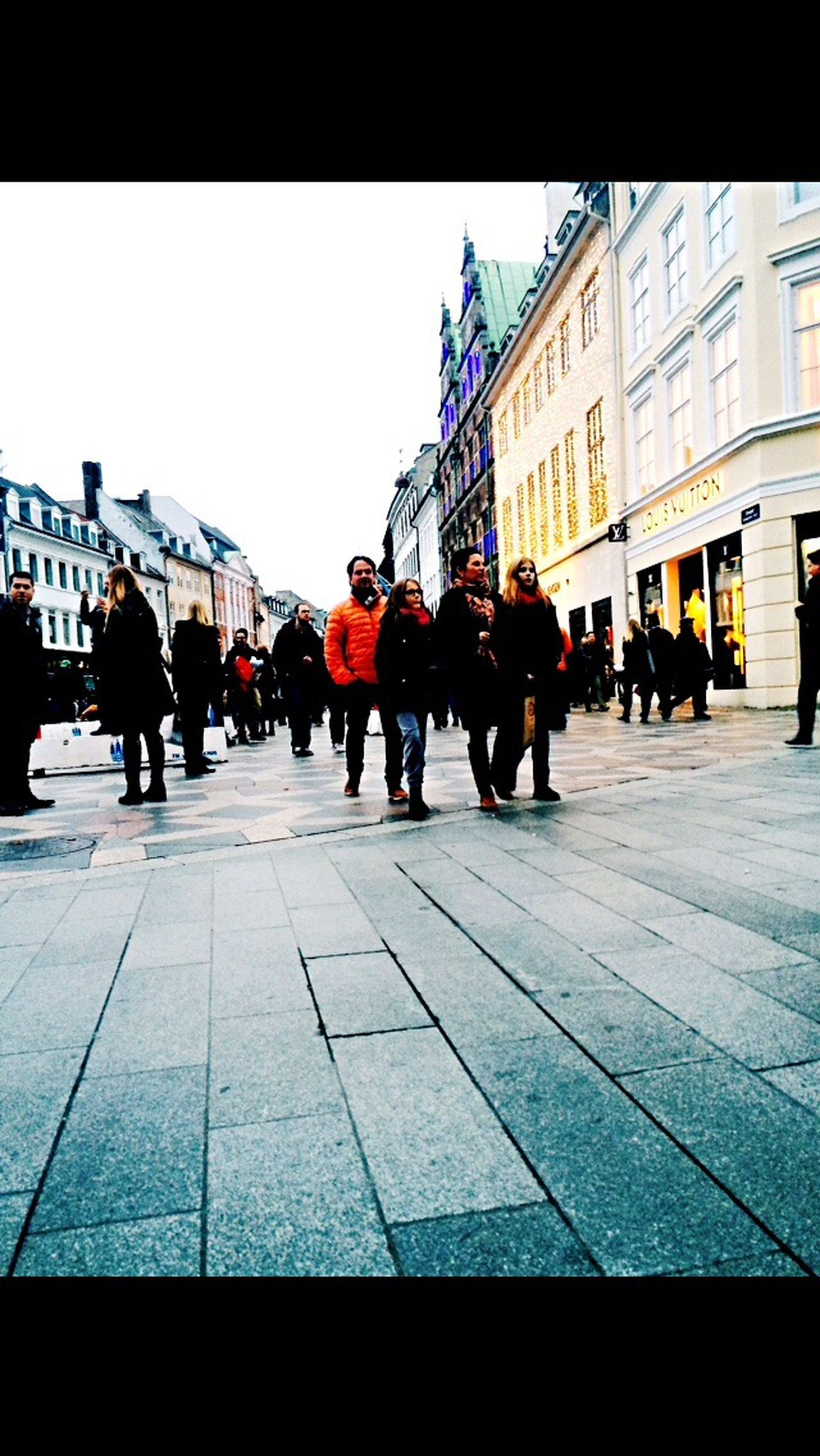 large group of people, building exterior, architecture, built structure, men, city, person, street, walking, city life, lifestyles, transfer print, clear sky, auto post production filter, mixed age range, city street, medium group of people, group of people, transportation