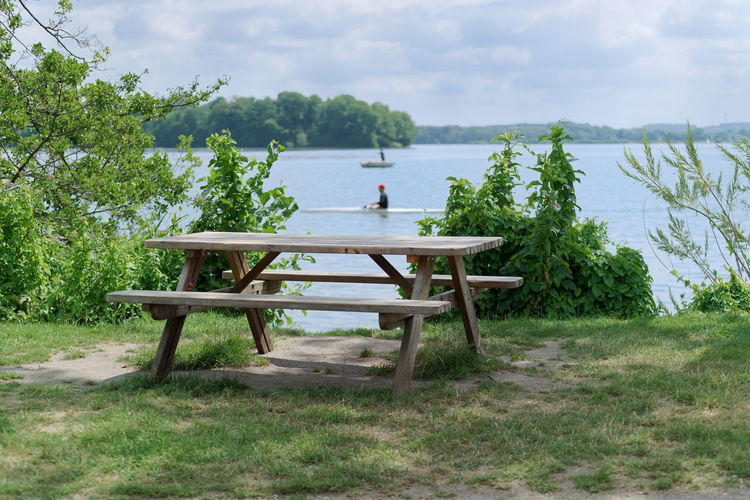 Picnic place at the lake coast - tranquil scene of wooden table with two benches at the lake coast Grass Tree Branches Beauty In Nature Bench Chair Cloud - Sky Coast Day Empty Green Color Nature No People Outdoors Picnic Table Plant Scenics - Nature Seat Sky Table Tranquil Scene Tranquility Tree Water Waterfront Watersports Moments Of Happiness