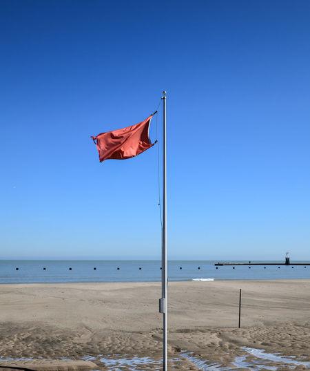 Flag on beach against clear blue sky