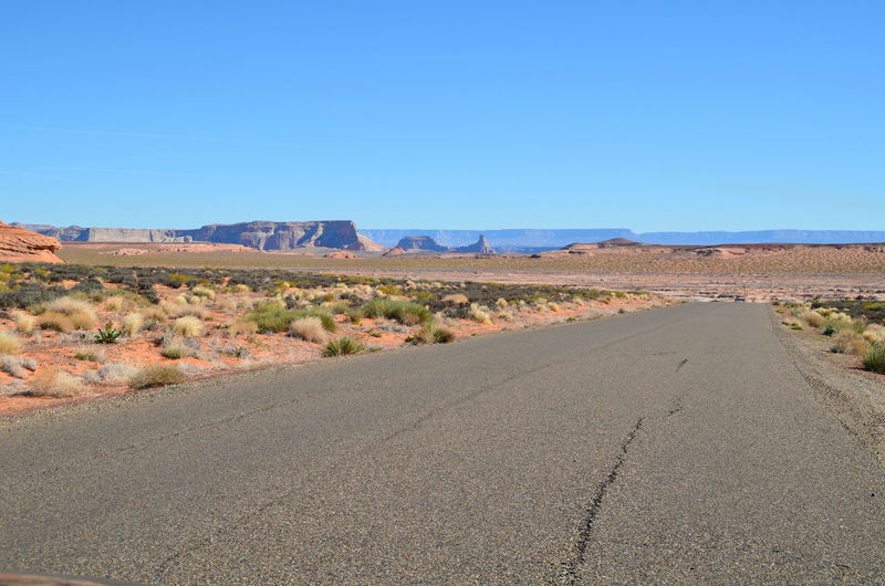 Empty road on landscape against clear blue sky at antelope canyon