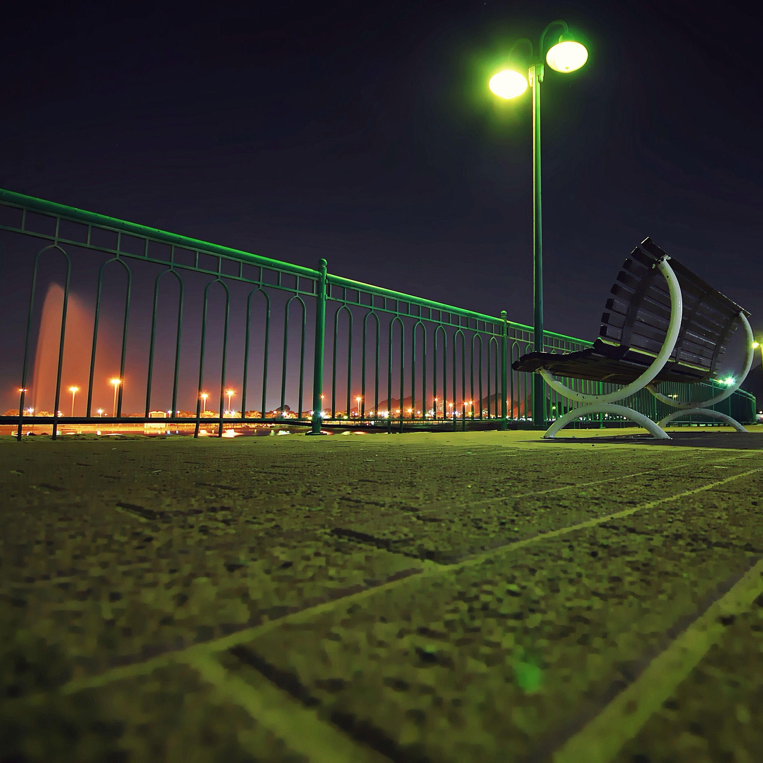 night, illuminated, lighting equipment, street light, green color, street, surface level, outdoors, light - natural phenomenon, grass, sport, city, built structure, building exterior, road, no people, incidental people, architecture, arts culture and entertainment, empty