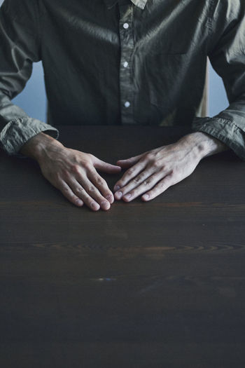 Midsection of man sitting by table