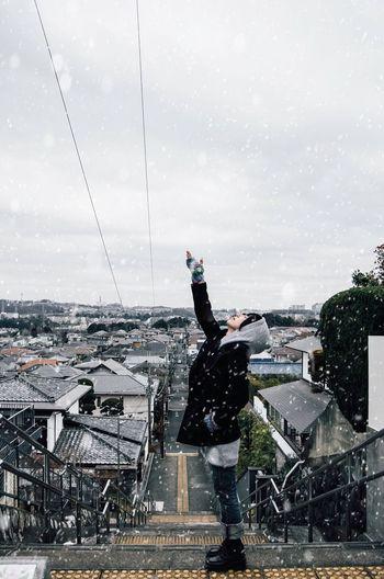 Man standing on wet street in city against sky