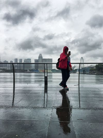 Woman Using Phone While Standing By Railing Against Marina Bay Financial Centre During Rainy Season