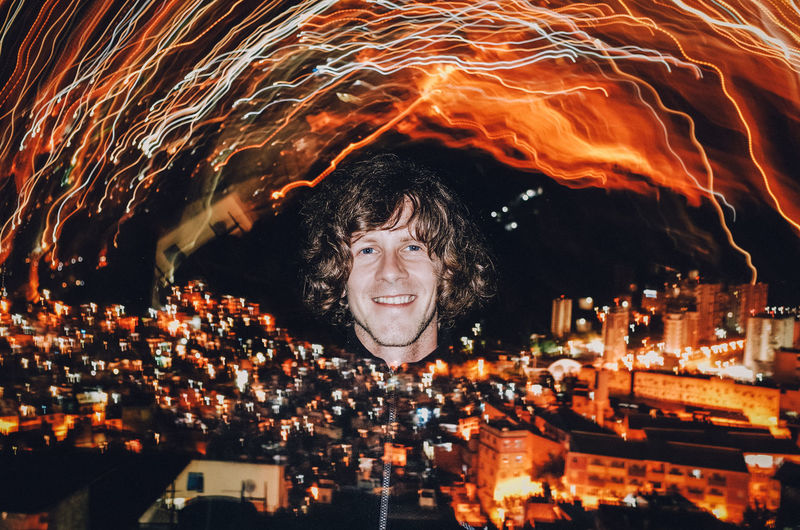 portrait of guy on fire, Rio de Janeiro - Brazil Double Exposure Rocinha Architecture Building Exterior City Cityscape Favela Flash Flash Photography Illuminated Lifestyles Light Trail Looking At Camera Night One Person Outdoors People Portrait Real People Rocinha Slum Sky Smiling Young Adult
