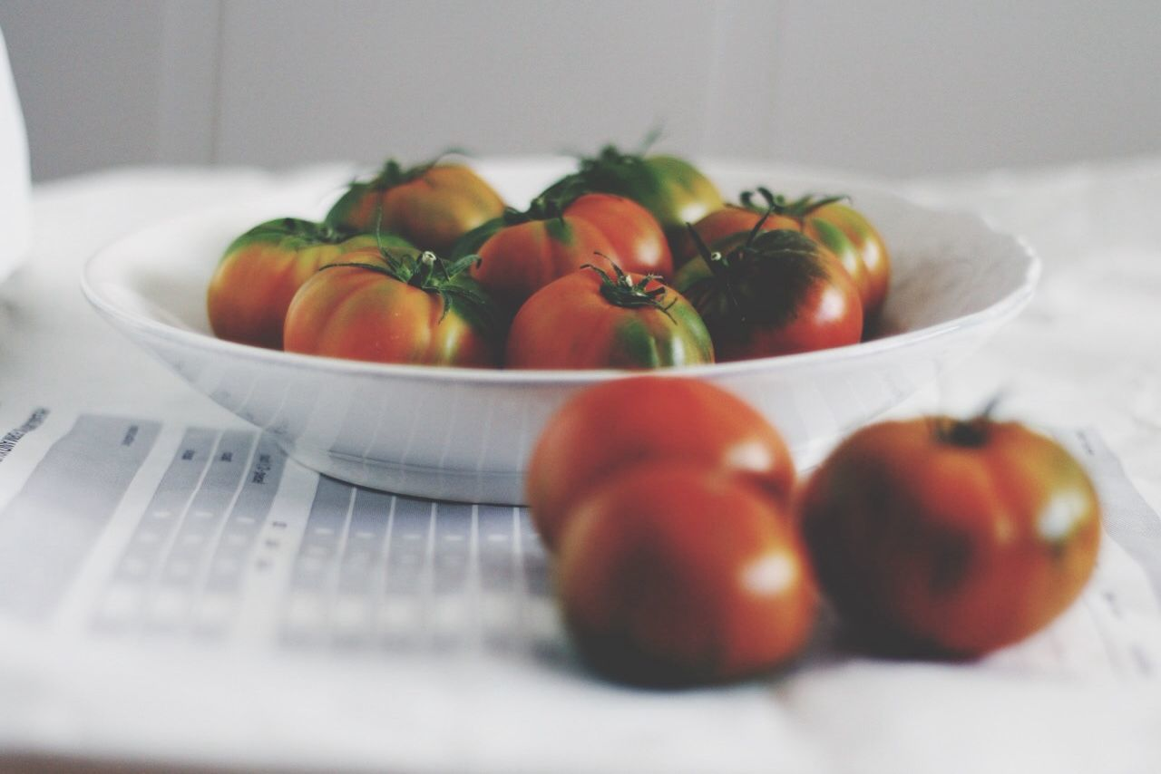 Tomatoes lying on white plate and on table