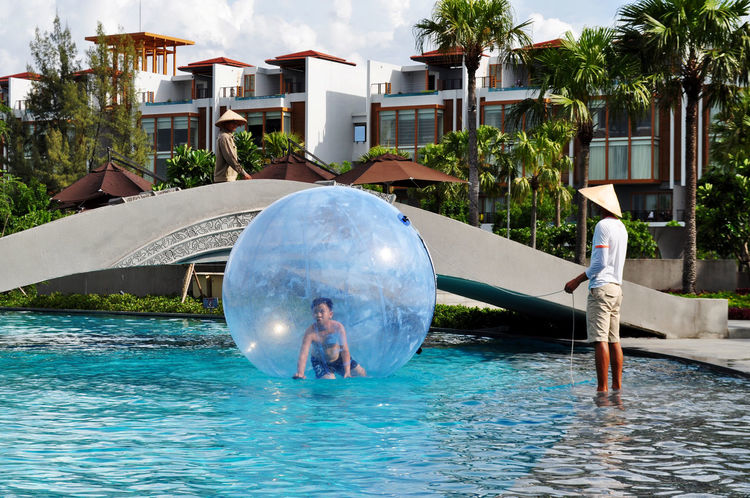 Boy playing in orb on swimming pool at resort in Vietnam. Activities Architecture Boys Bridges Built Structure Color Of Sport Conical Hats Editorial  Floating Fun Leisure Lifestyle Lăng Cô Orbs Outdoors Playing Recreation  Resorts Supervision Swimming Pool Tourism Tree Vietnam Water