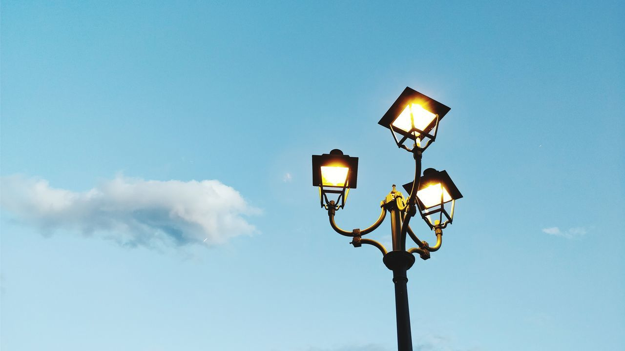 sky, lighting equipment, low angle view, street light, illuminated, street, electricity, cloud - sky, light, nature, electric light, copy space, blue, outdoors, no people, technology, pole, glowing, day, electric lamp, electrical equipment