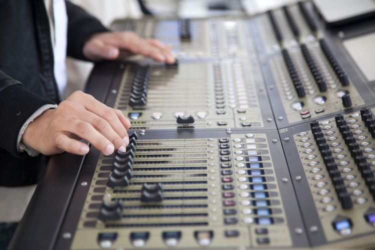 Technician adjusting sound mixers at studio