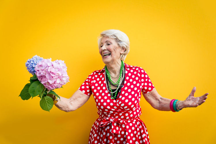 Senior woman holding flower standing against colored background