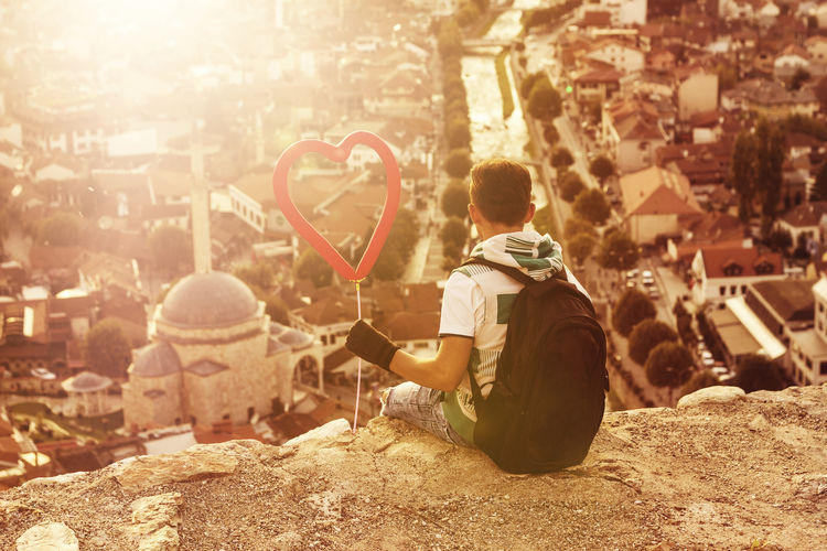 Rear View Of Boy Holding Heart Shape Balloon While Sitting On Cliff Against Sinan Pasha Mosque