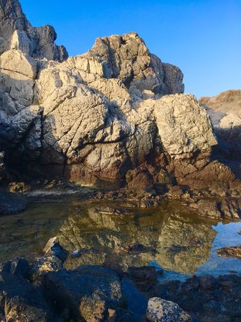 Visit Oman Rock Formation Clear Sky Eroded Tranquil Scene Rock - Object Textured  Geology Scenics Physical Geography Water Tranquility Beauty In Nature Nature Rough Cliff Rocky Mountains Non-urban Scene Rocky Blue Mountain Beach Combing Rock Pools Reflections In The Water