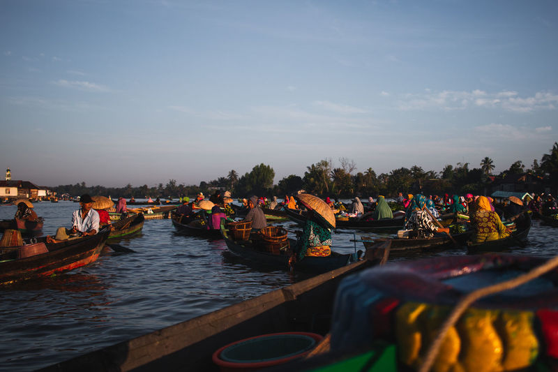People in boats at floating market on river