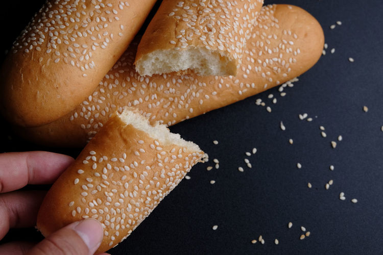 Cropped hand of person holding sliced bread on table