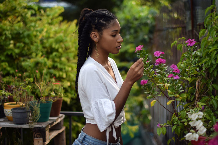 Young woman looking down while standing on flowering plants