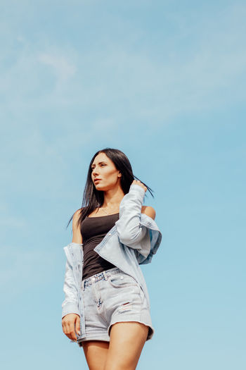 Low angle view of young woman standing against sky
