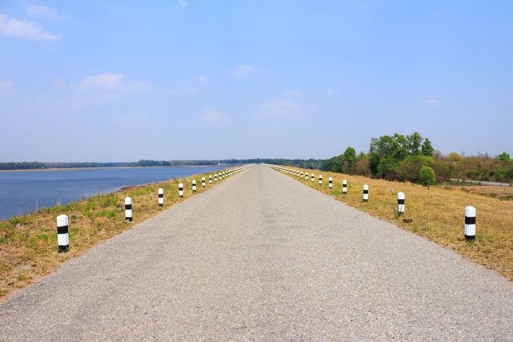 Empty road along calm sea against sky