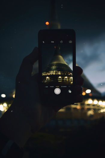 Close-up of hand photographing illuminated smart phone at night