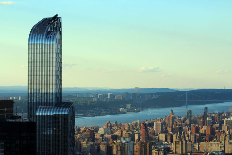 Modern building with cityscape by east river against sky