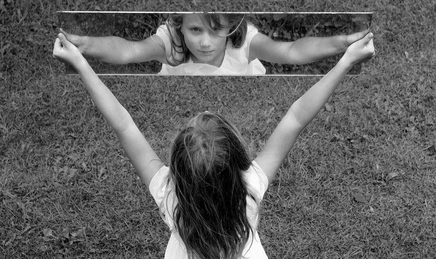 Girl with arms raised holding mirror with reflection on grass