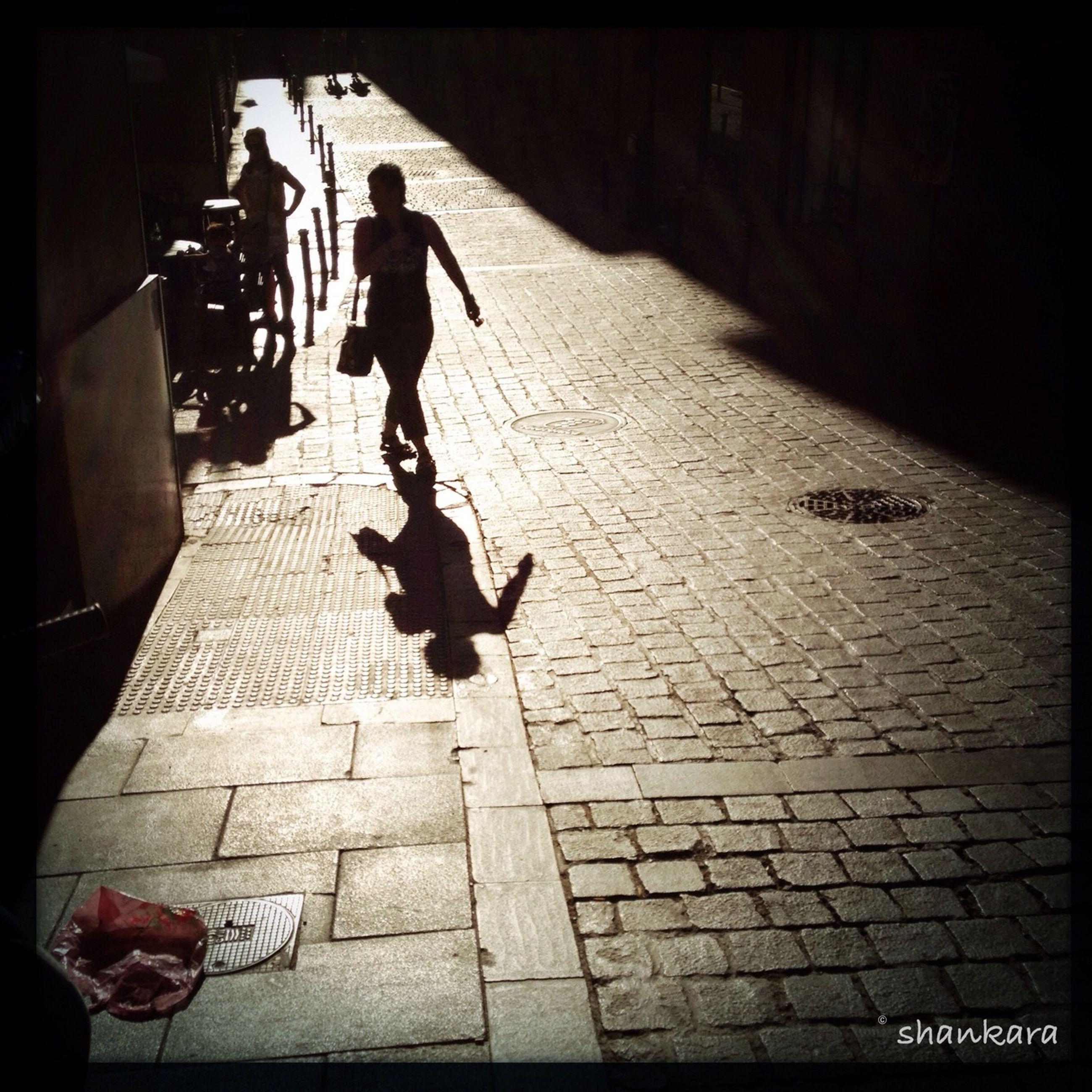 transfer print, auto post production filter, lifestyles, men, street, full length, bicycle, shadow, leisure activity, cobblestone, walking, sidewalk, transportation, person, sunlight, paving stone, city life