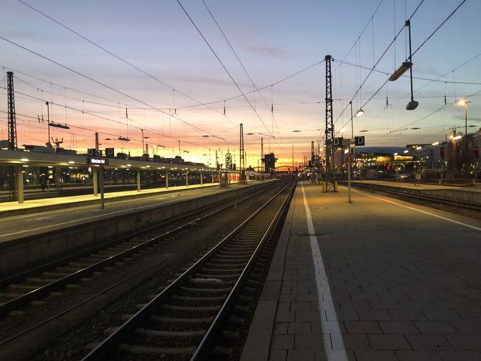 Railroad station platform against sky at sunset
