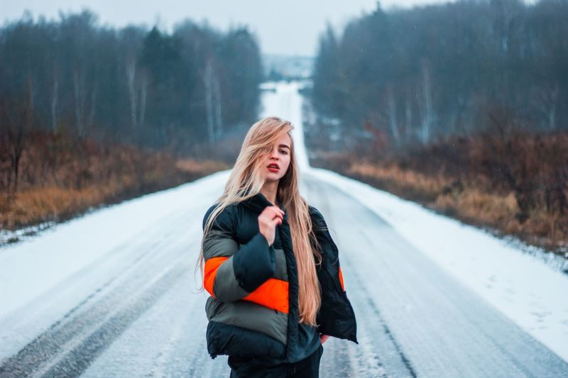 Woman standing on snow covered road