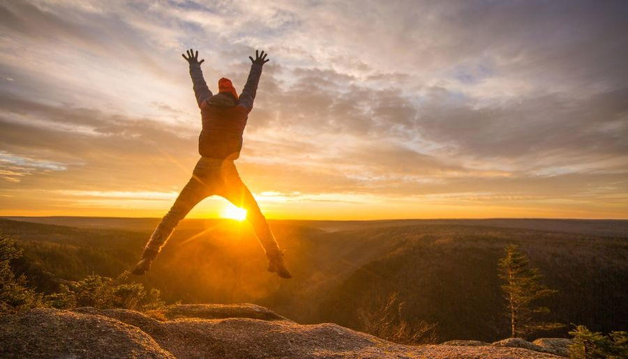 Young man with arms outstretched against sunset sky