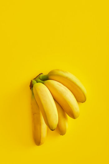 Close-up of bananas over yellow background