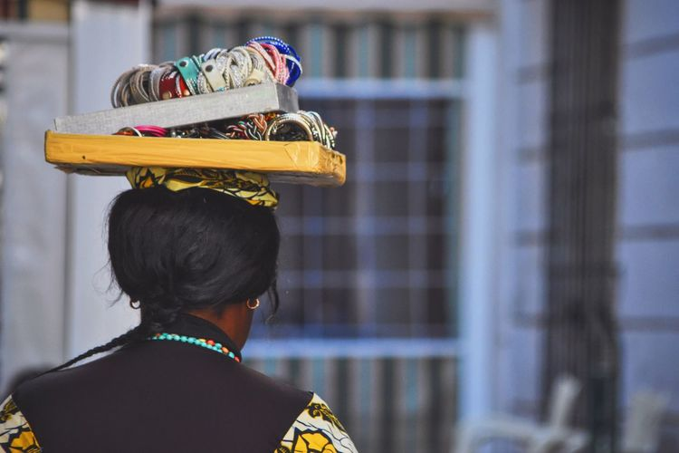 Rear view of woman carrying ornaments on head